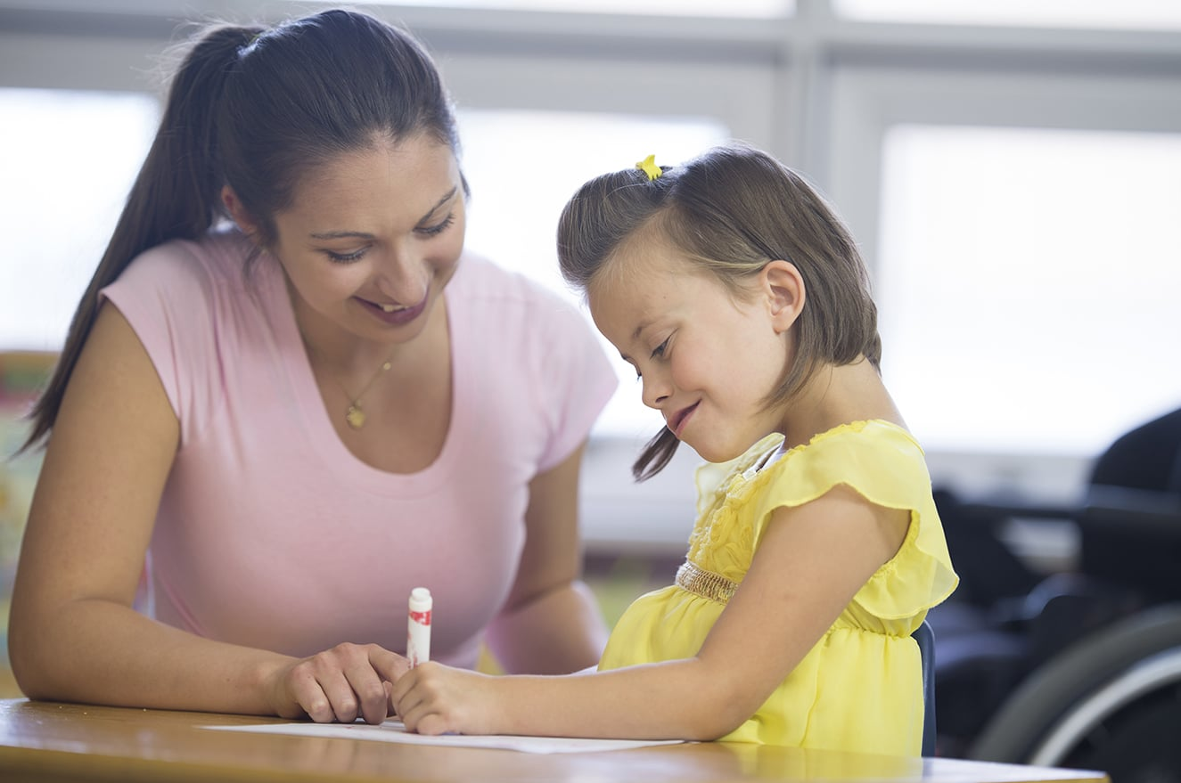 A caregiver is a helping a disabled girl with a coloring project at school.
